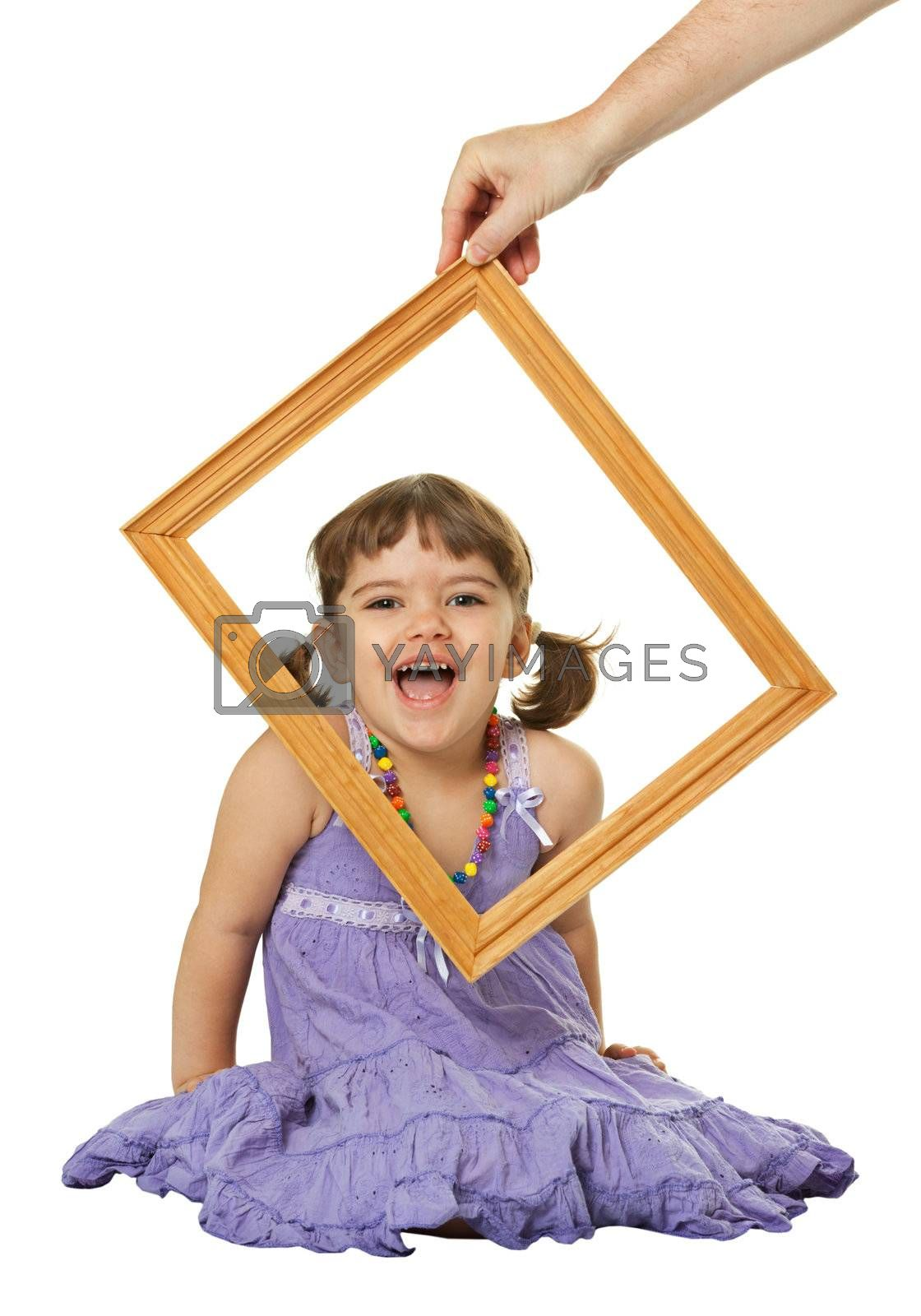 Happy little girl looking through the frame isolated on white background