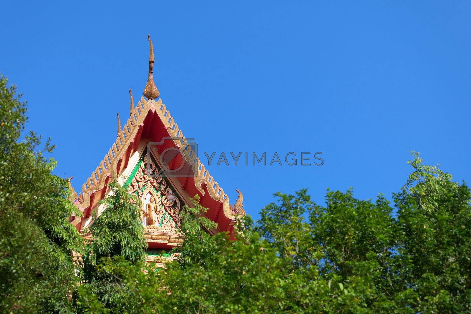 The roof of a Thai Buddhist monastery over the trees
