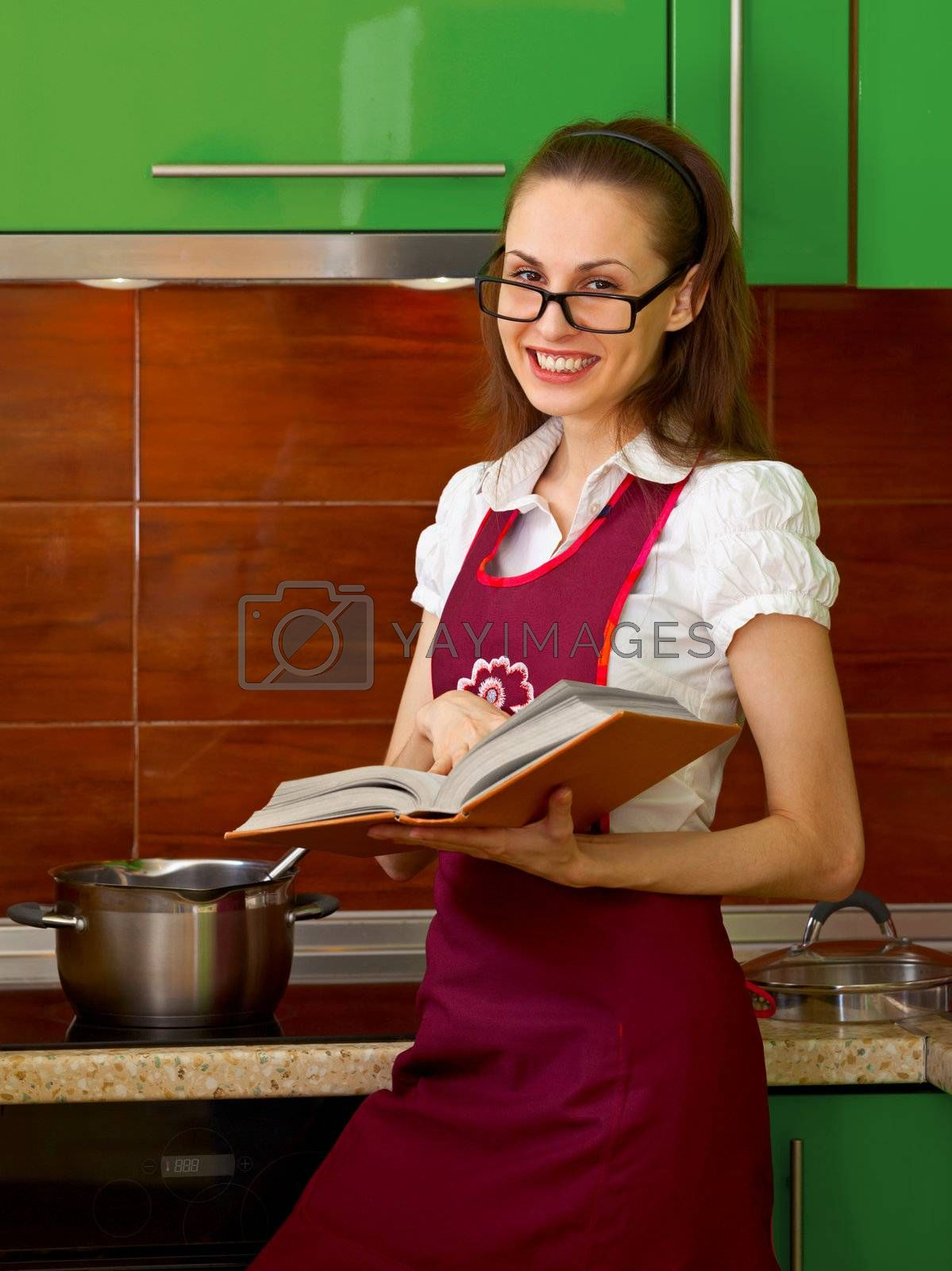 A young woman prepares a meal on kitchen, using the cook book