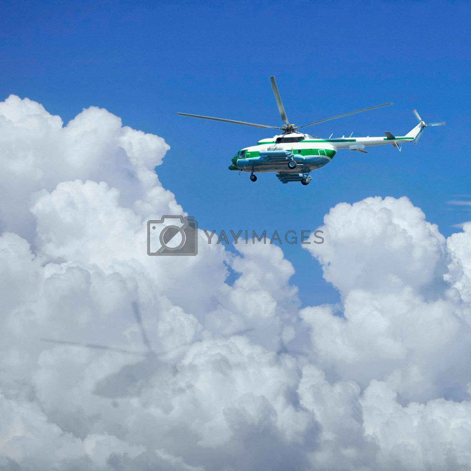 The helicopter is flying above the clouds