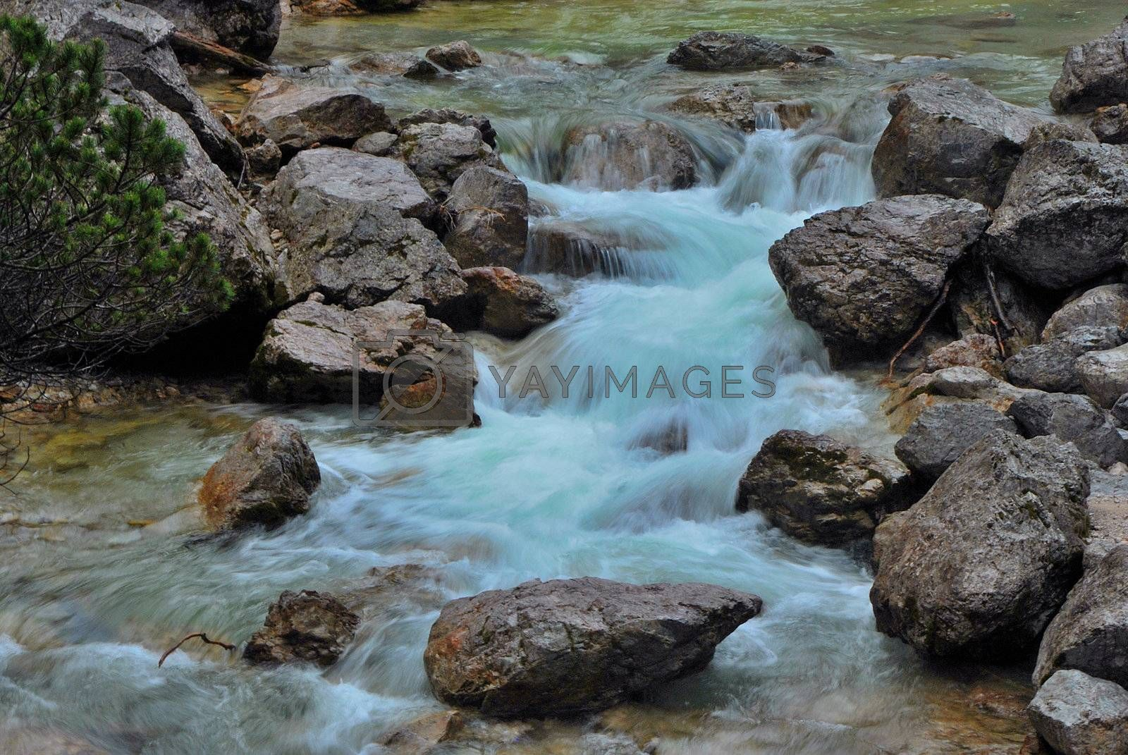 cold blue water of a torrent in the mountain and summer