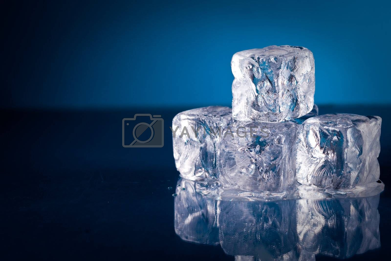Frozen ice cubes on blue background with reflection