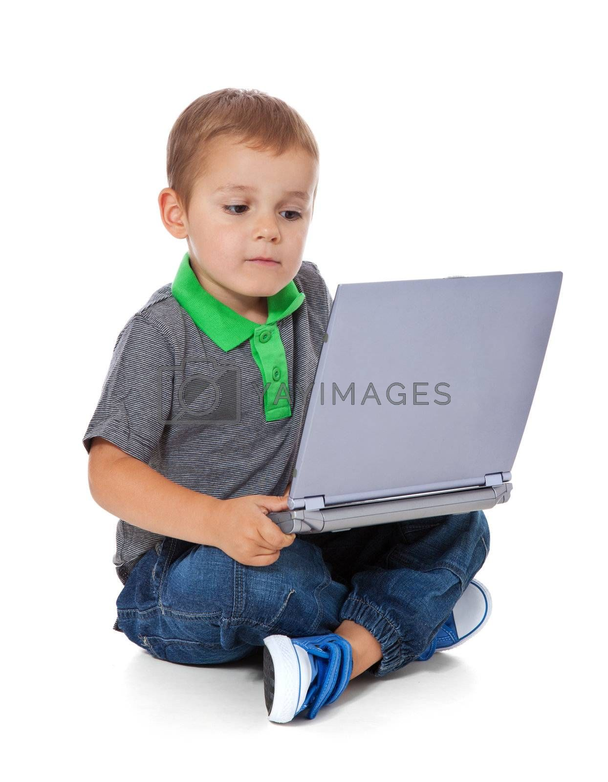 Full length shot of a cute little boy sitting on the floor with a computer. All isolated on white background.