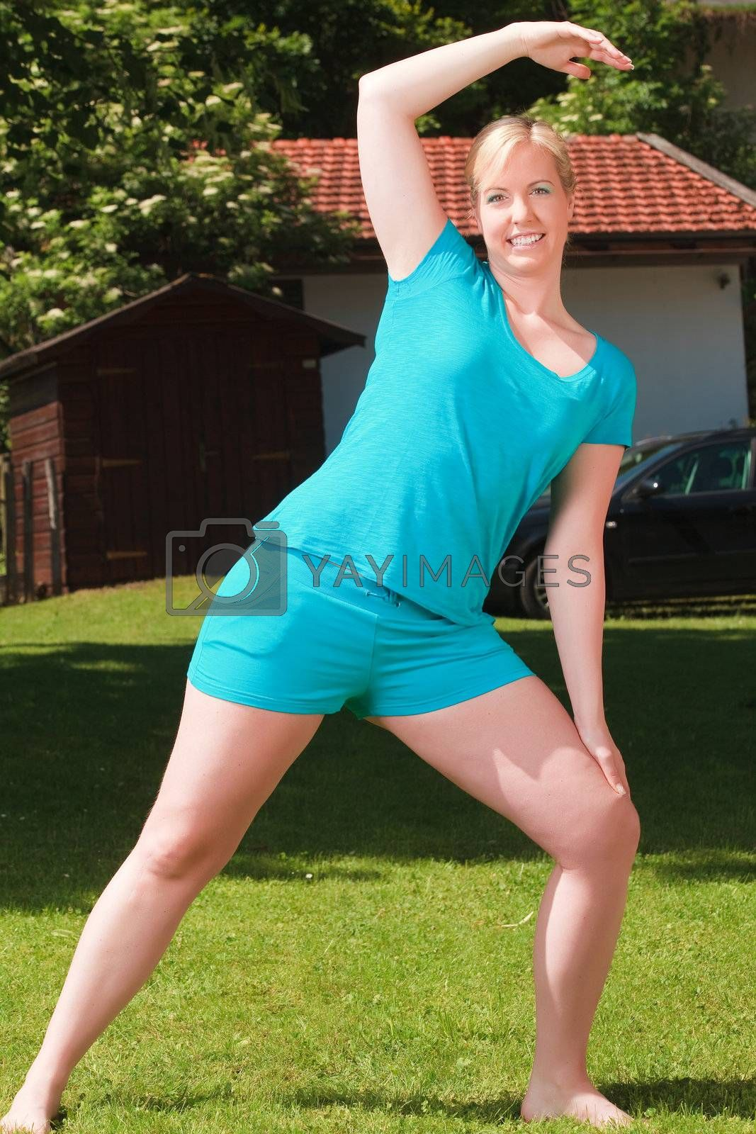 Young woman doing gymnastics on a green meadow