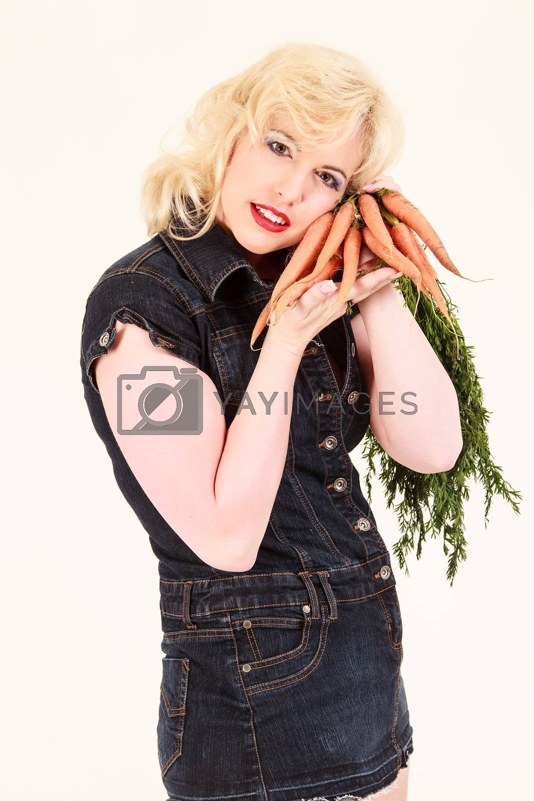 Attractive blond woman holding carrots on the cheek