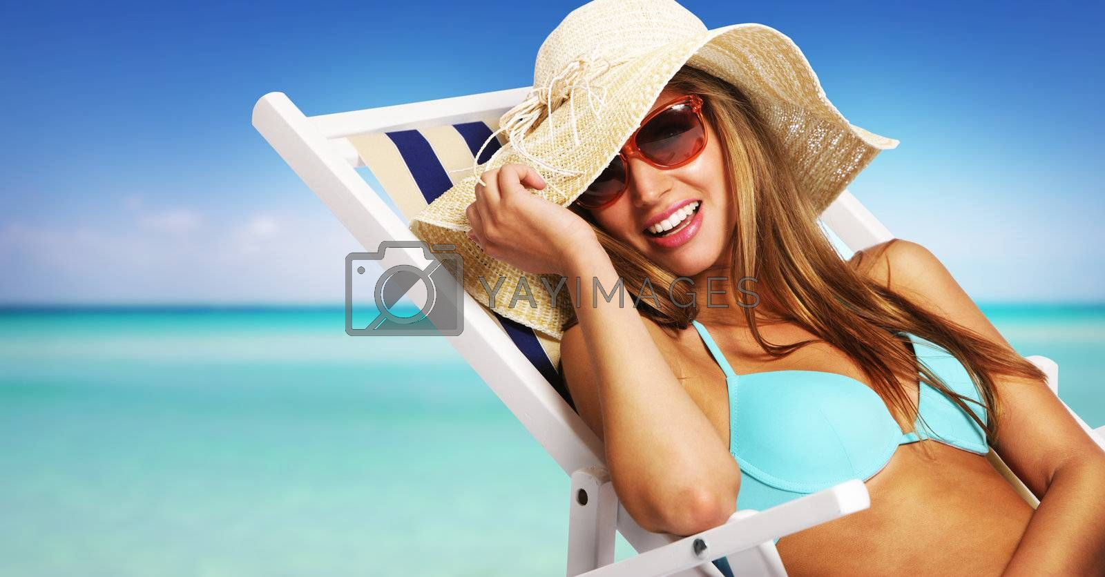 Smiling young woman relaxing on beach chair