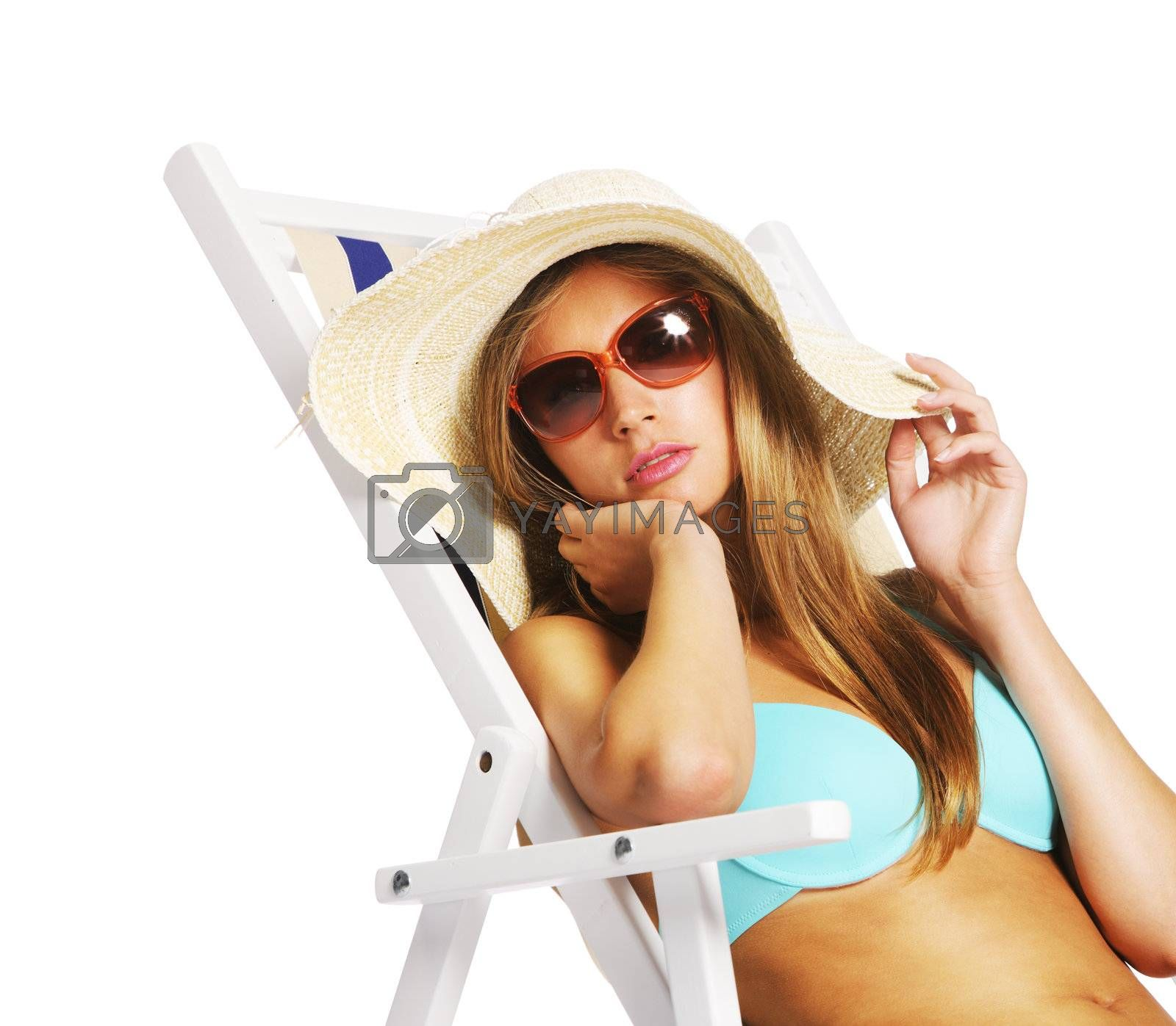 Beautiful young woman relaxing on beach chair, isolated on white background