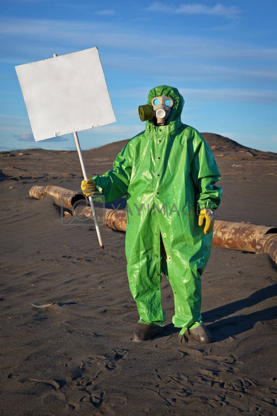 Scientist chemist with a placard in his hand in the area of chemical contamination