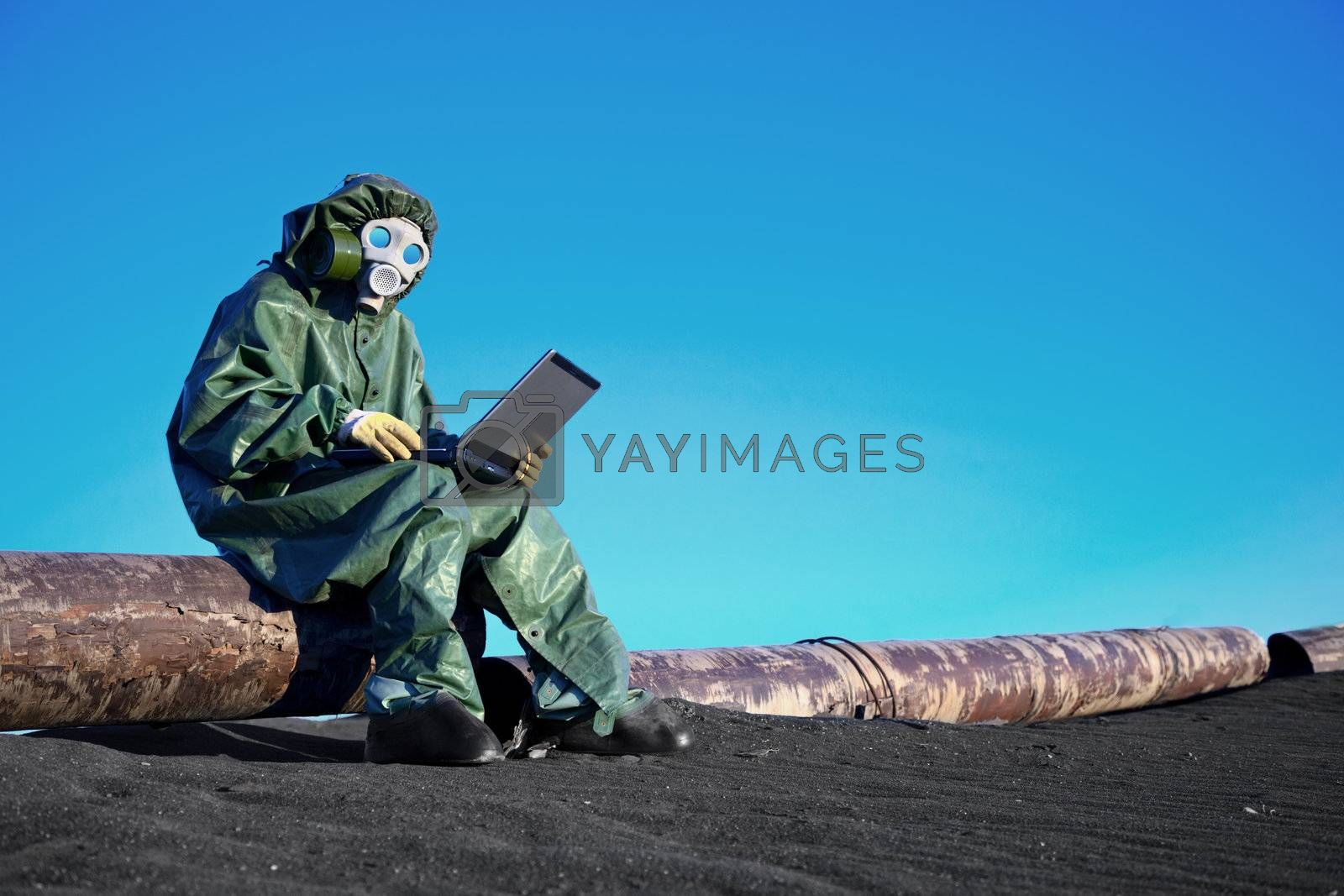 A scientist working with a laptop on a chemically contaminated area