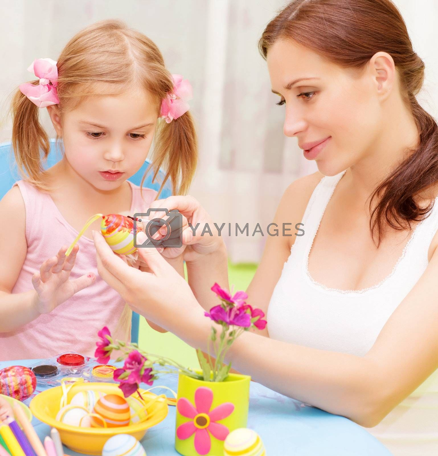 Closeup portrait of cute little baby girl with beautiful young mother paint Easter eggs, traditional Christian symbol