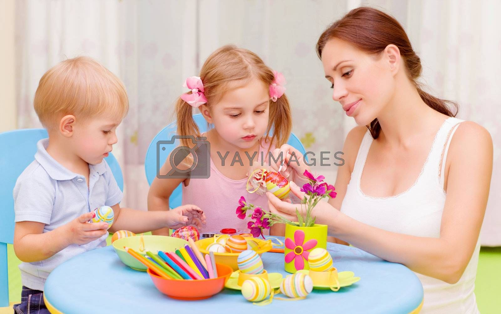 Two little kids with young teacher paint Easter eggs, art lesson, interacting children in daycare, Christian holiday concept