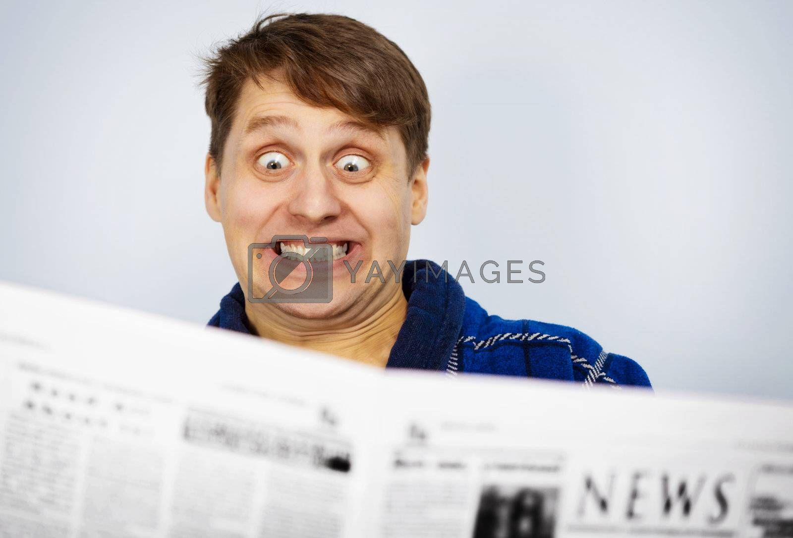 Man shocked while reading the news from newspapers