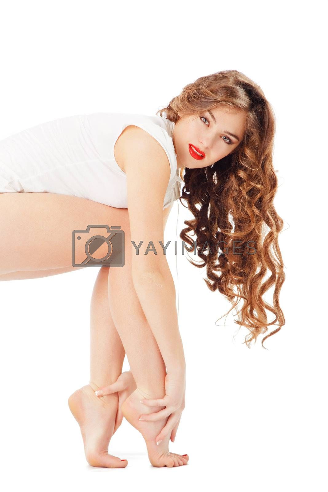 Studio shot of beautiful sexy woman showing her legs and long curly hair