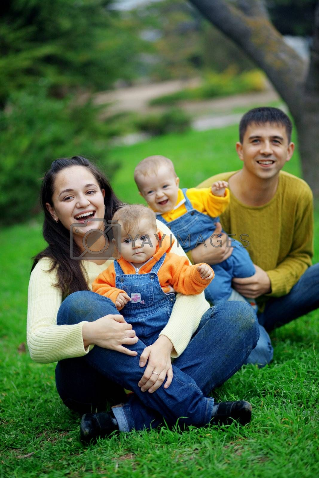 Portrait of happy young parents with their two babies twins having fun in park