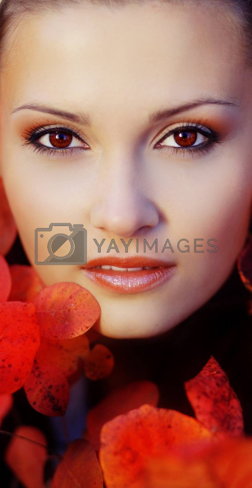 Close-up portrait of beautiful face in red autumn leaves