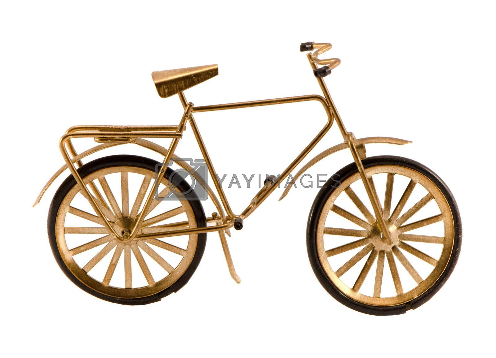 Small gold color toy bicycle isolated on white background.