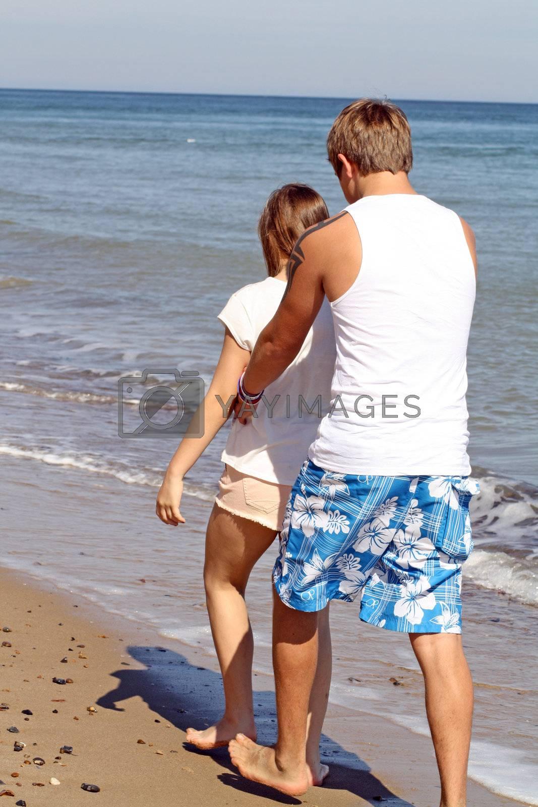 teenagers walking along the beach