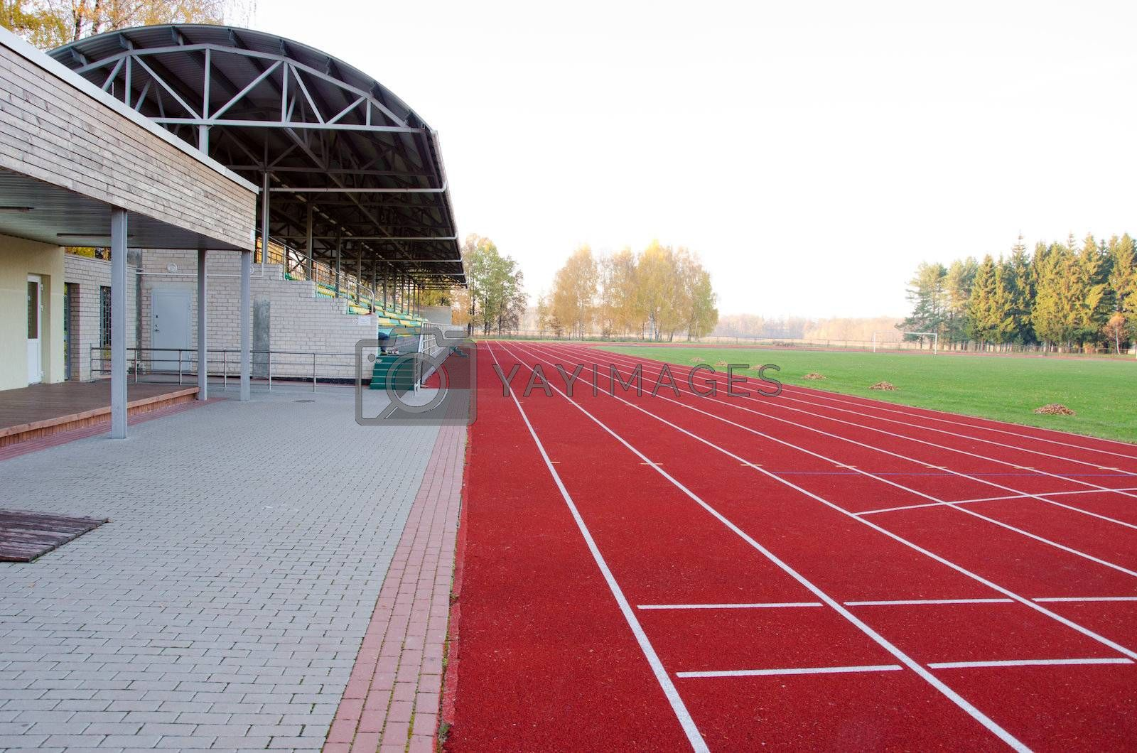 Athletics stadium with running tracks and stands and football pitch in middle
