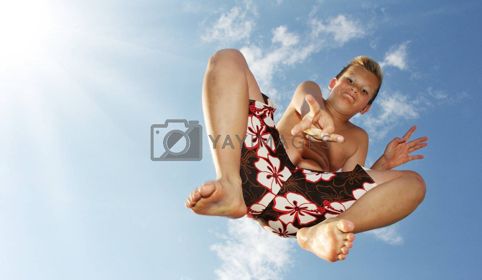 Little boy is jumping in front of the sky showing victory sign