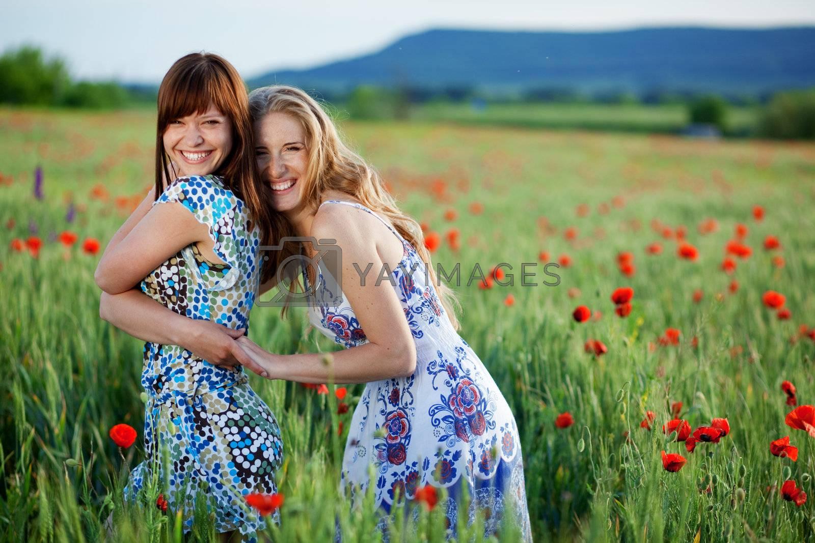 Two happy smiling girls in poppy field