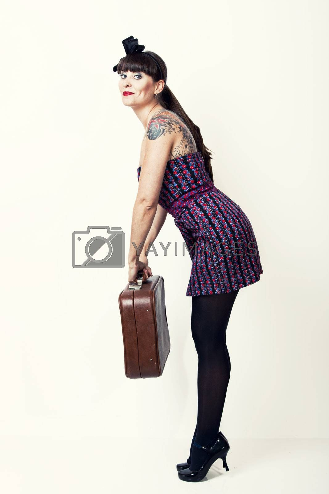 Portrait of a beautiful woman with a vintage look posing with a suitcase