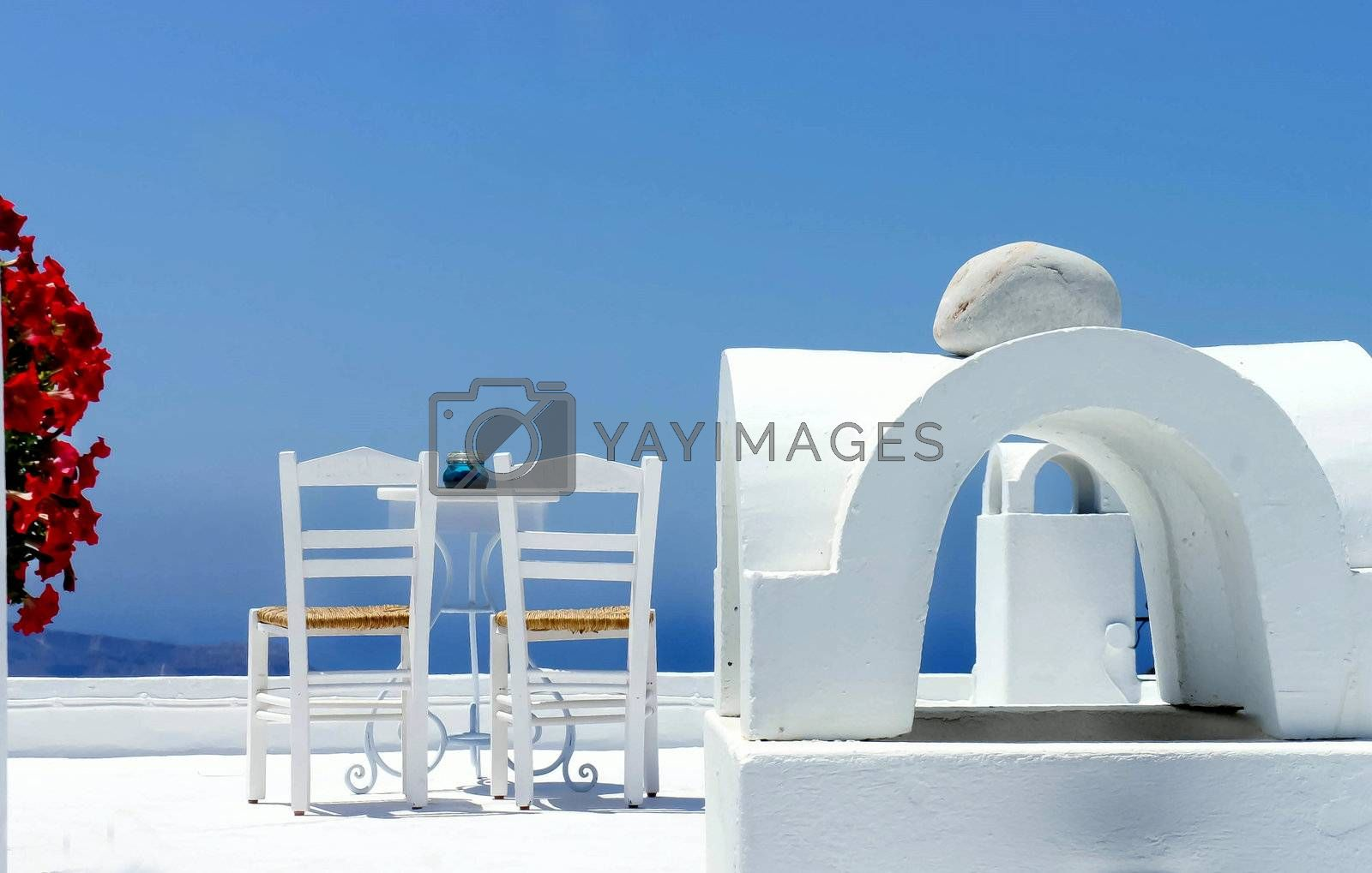 Santorini cosy terrace with two chairs and flowers