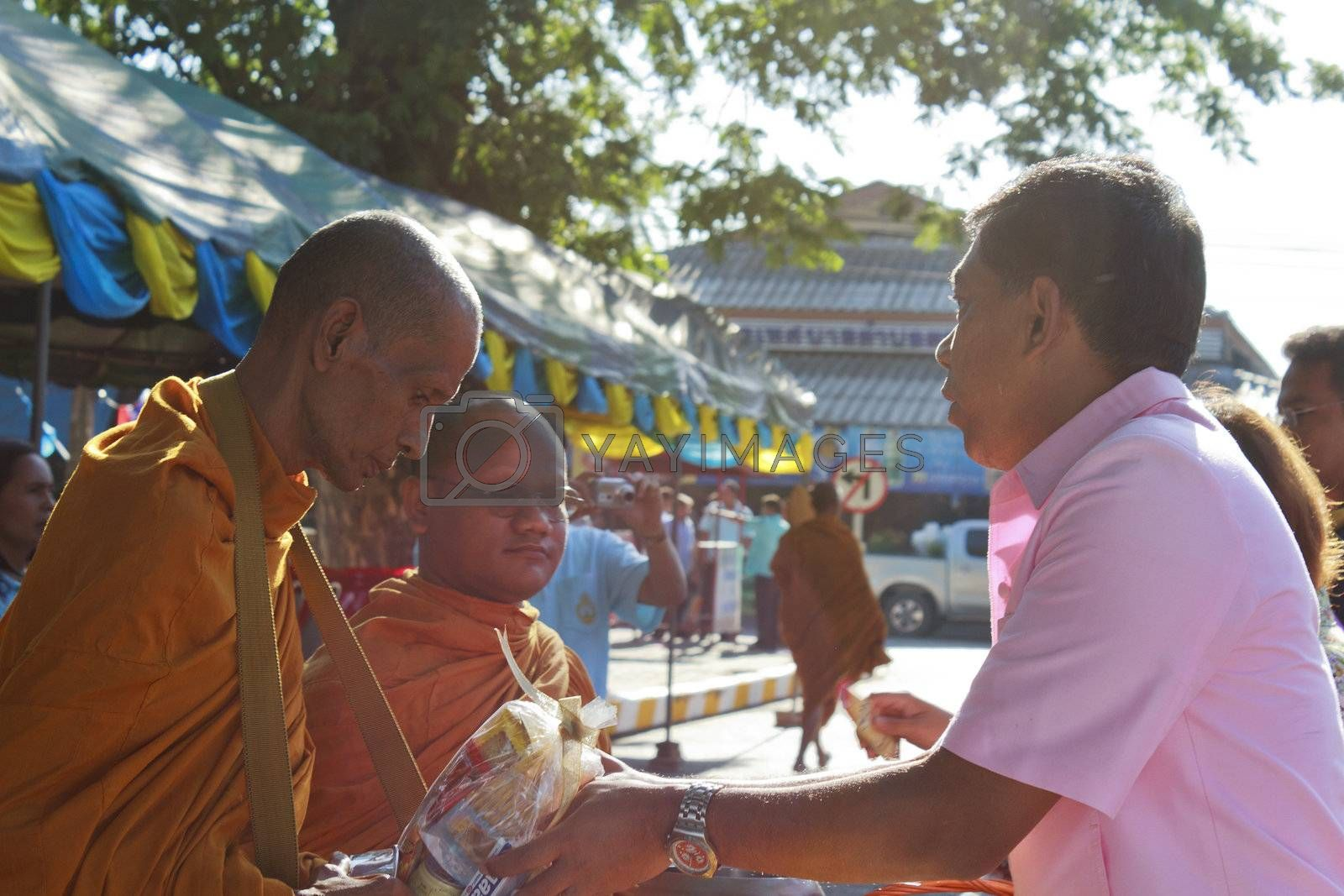 SURAT THANI, THAILAND - AUGUST 12, 2012 : Mr.Suriyan Jirasatsuntorn Chiya sheriff give food offerings to Buddhist monks during celebrated Mother's day as the birthday of Her Majesty Queen Sirikit at Chiya on August 12, 2012 in Surat Thani, Thailand.
