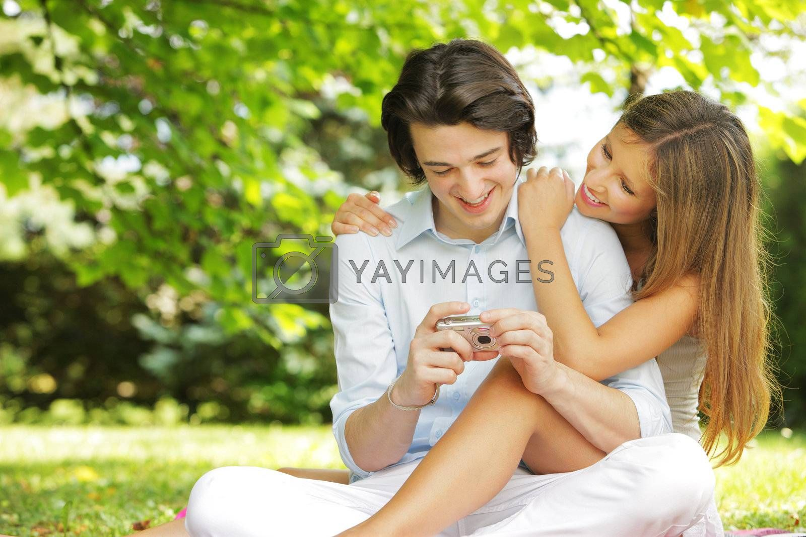 a couple of lovers, view photos on the display of their compact camera