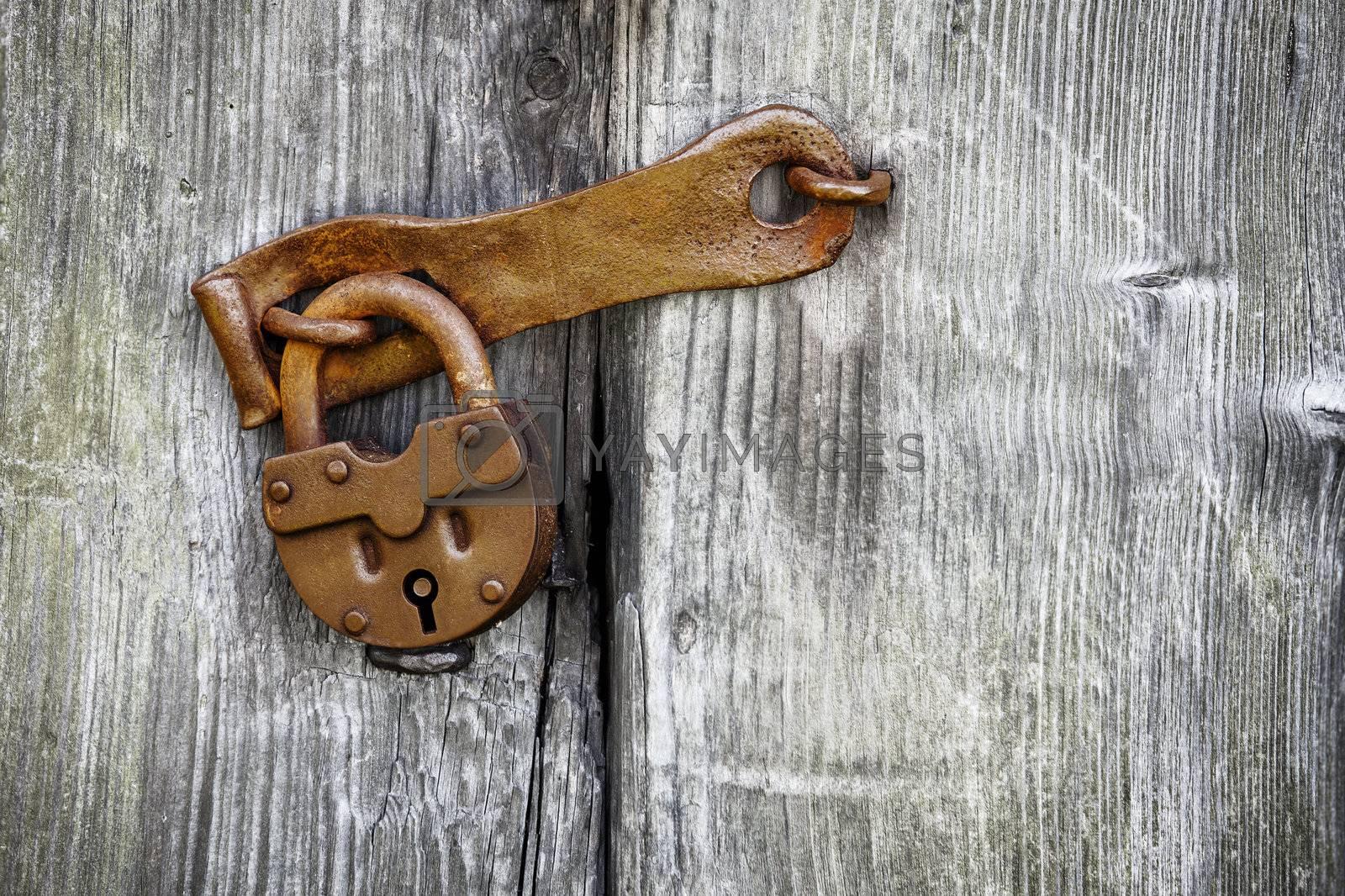 Old rusty padlock on a wooden door