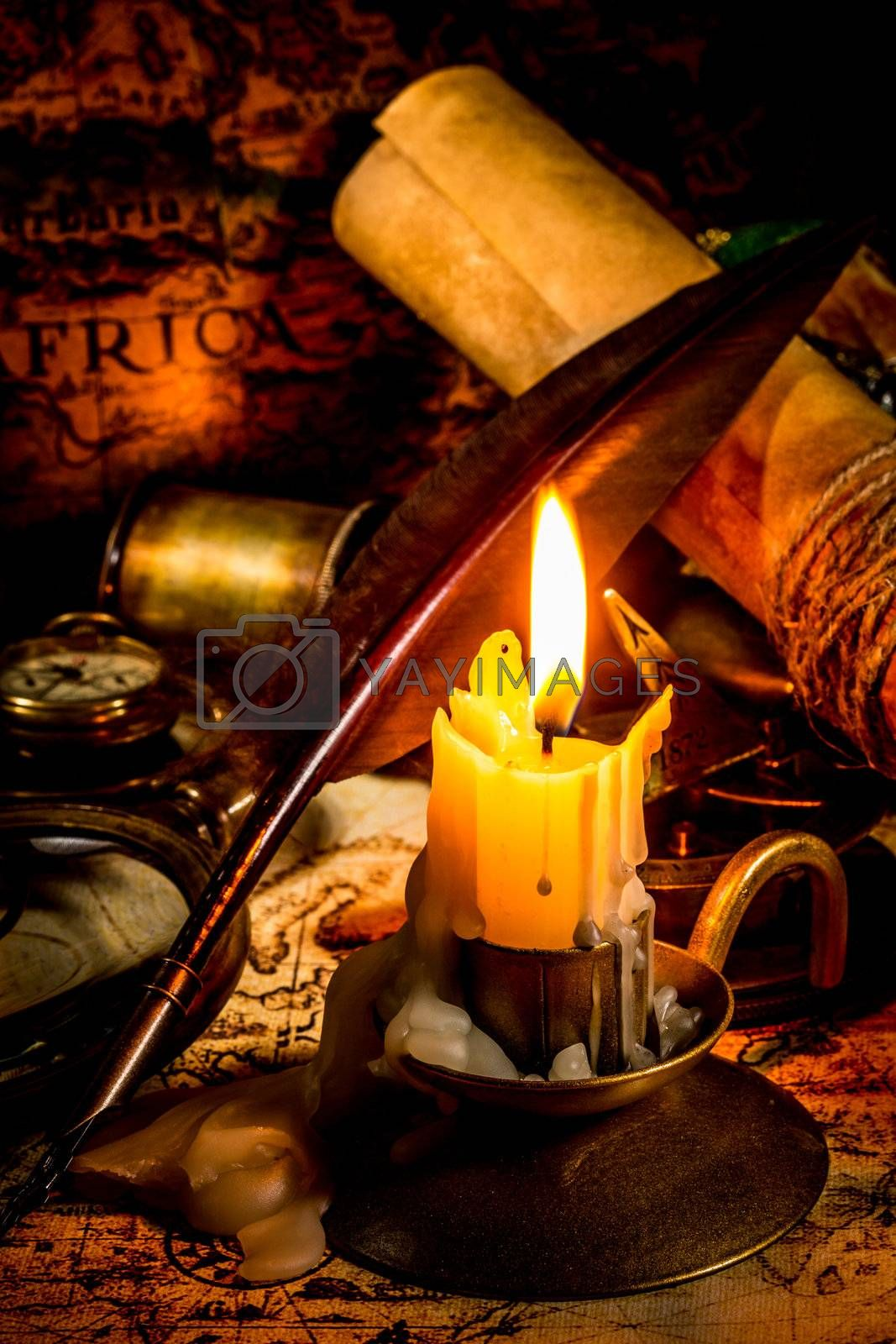 Vintage compass, magnifying glass, quill pen, spyglass lie on an old ancient map with a lit candle