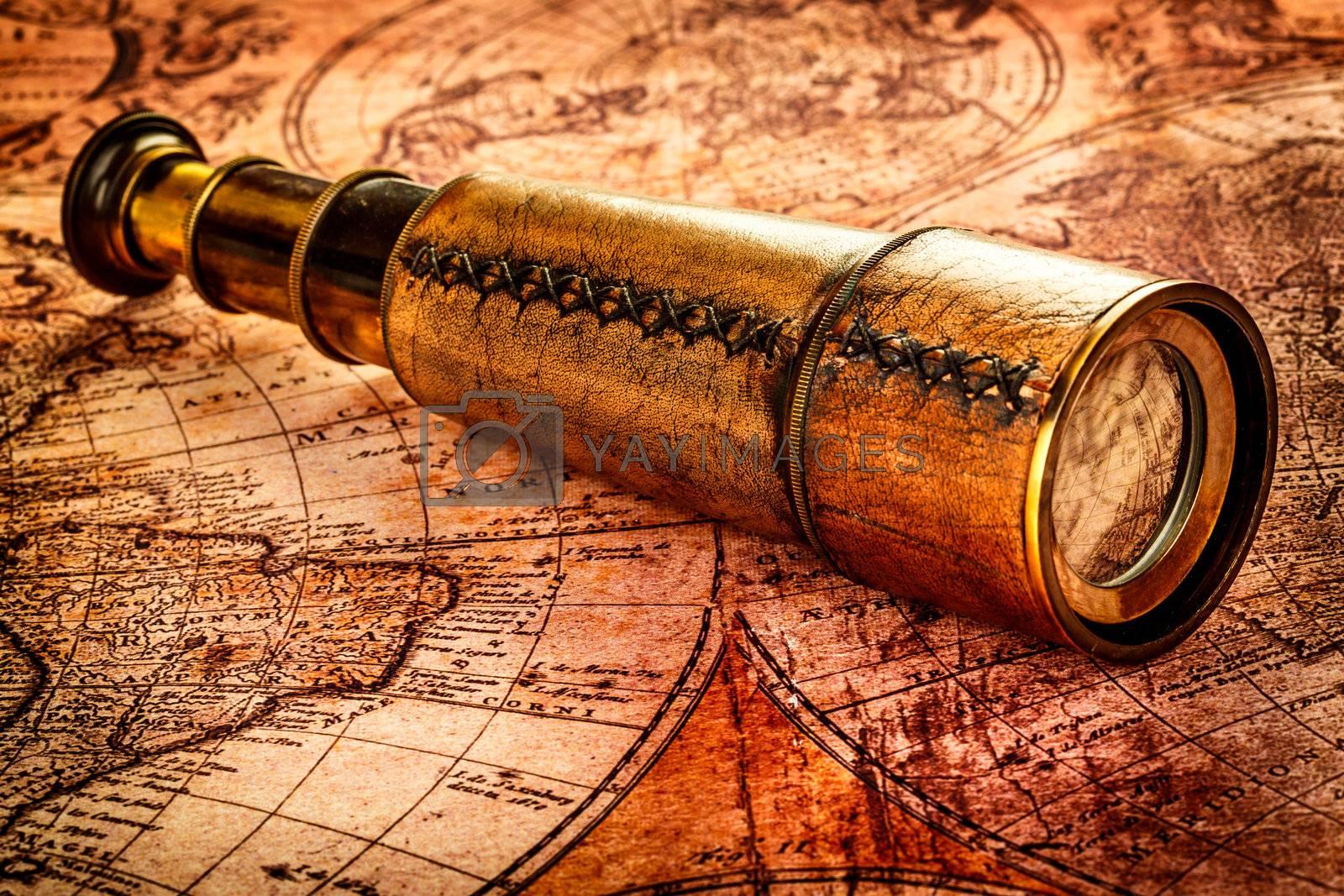 Vintage still life. Vintage spyglass lies on an ancient world map