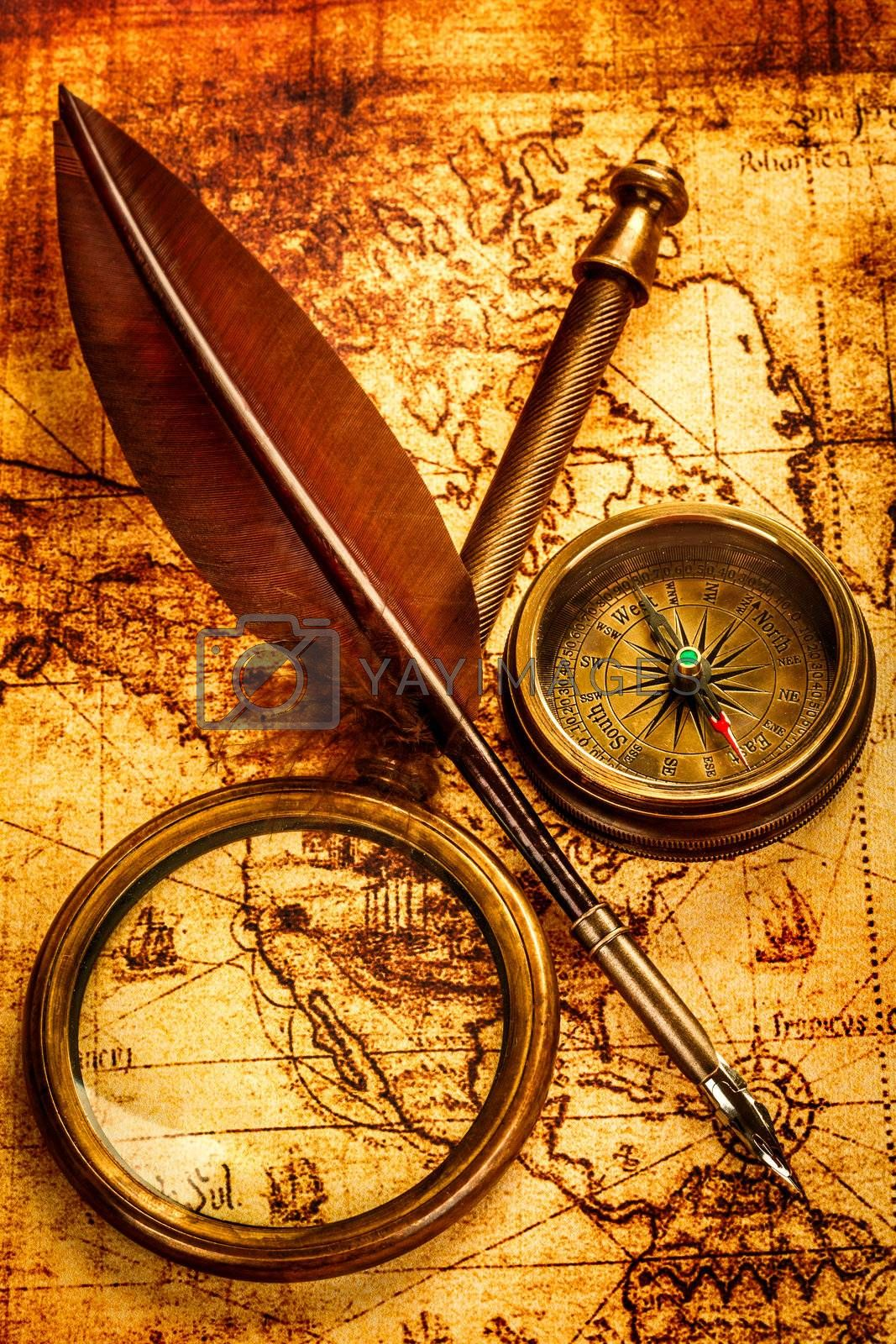 Vintage magnifying glass, compass and goose quill pen lying on an old map.