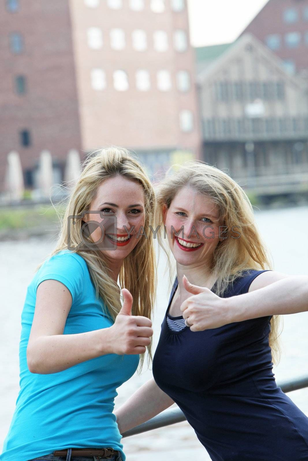 Happy female friends standing alonside an urban waterway giving an enthusiastic thumbs up of approval for their lifestyle Happy female friends standing alonside an urban waterway giving a thumbs up of approval for their lifestyle