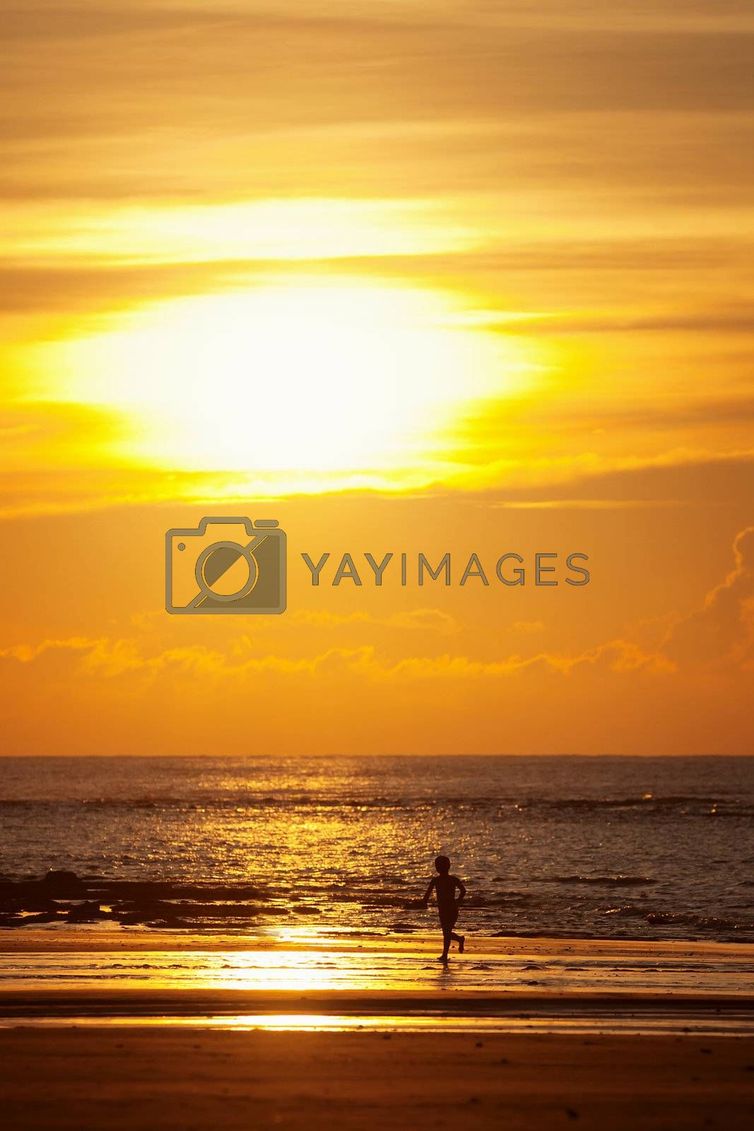 Sunset on a tropical beach and silhouette of a kid