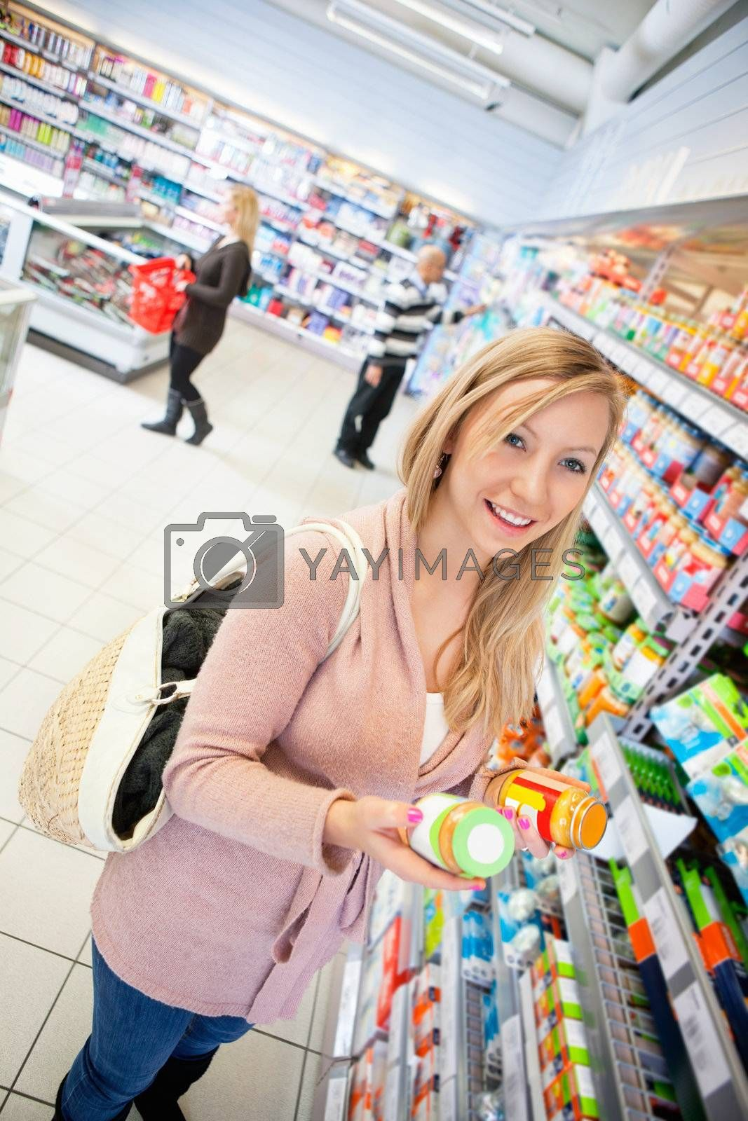 Happy young woman holding jar in the supermarket with people in the background