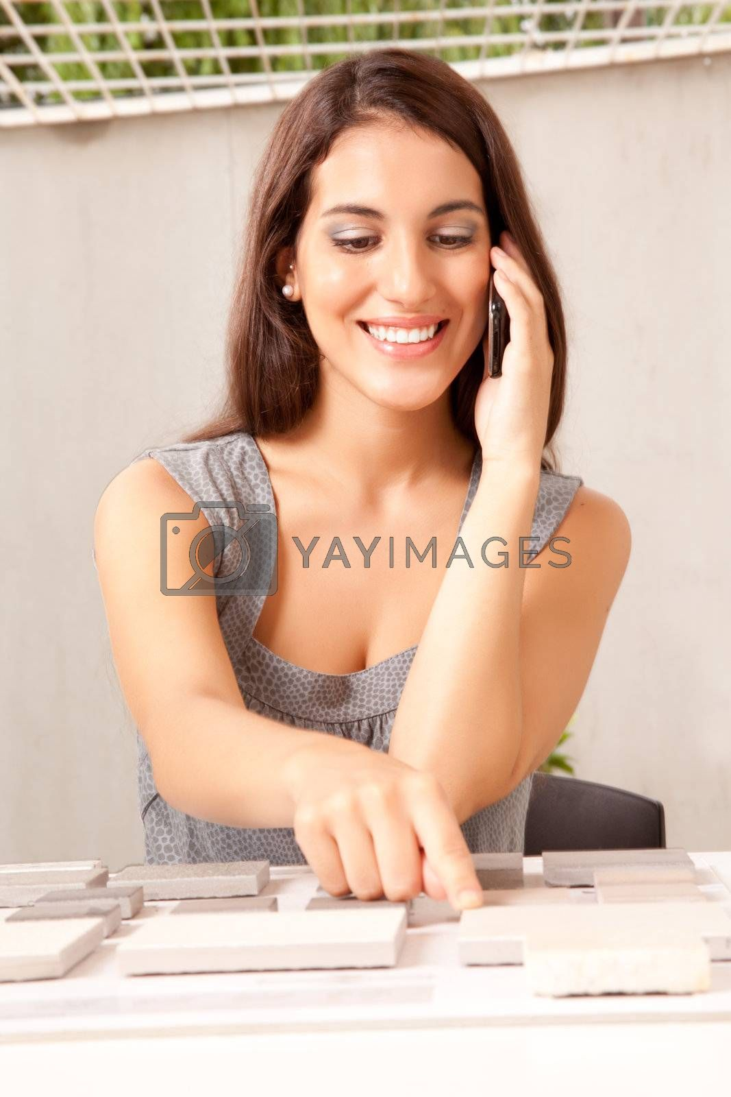 An interior designer / architect on the phone choosing a stone sample swatch