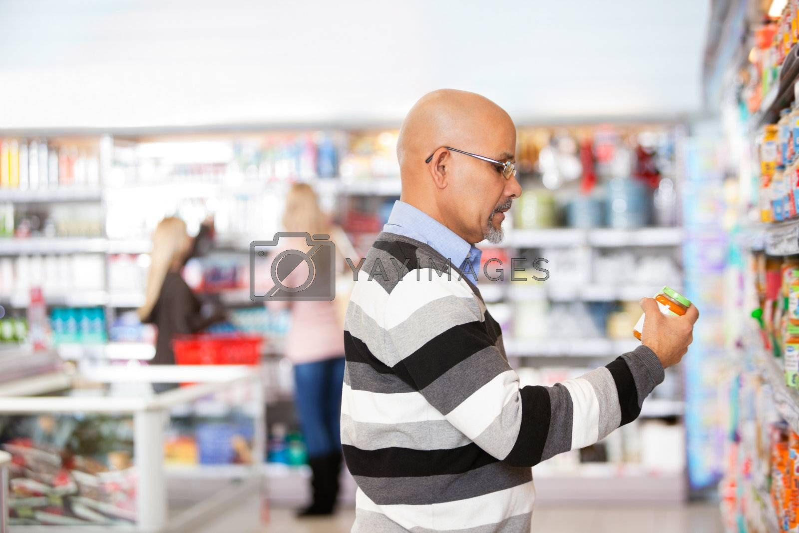 Mature man shopping in the supermarket with people in the background