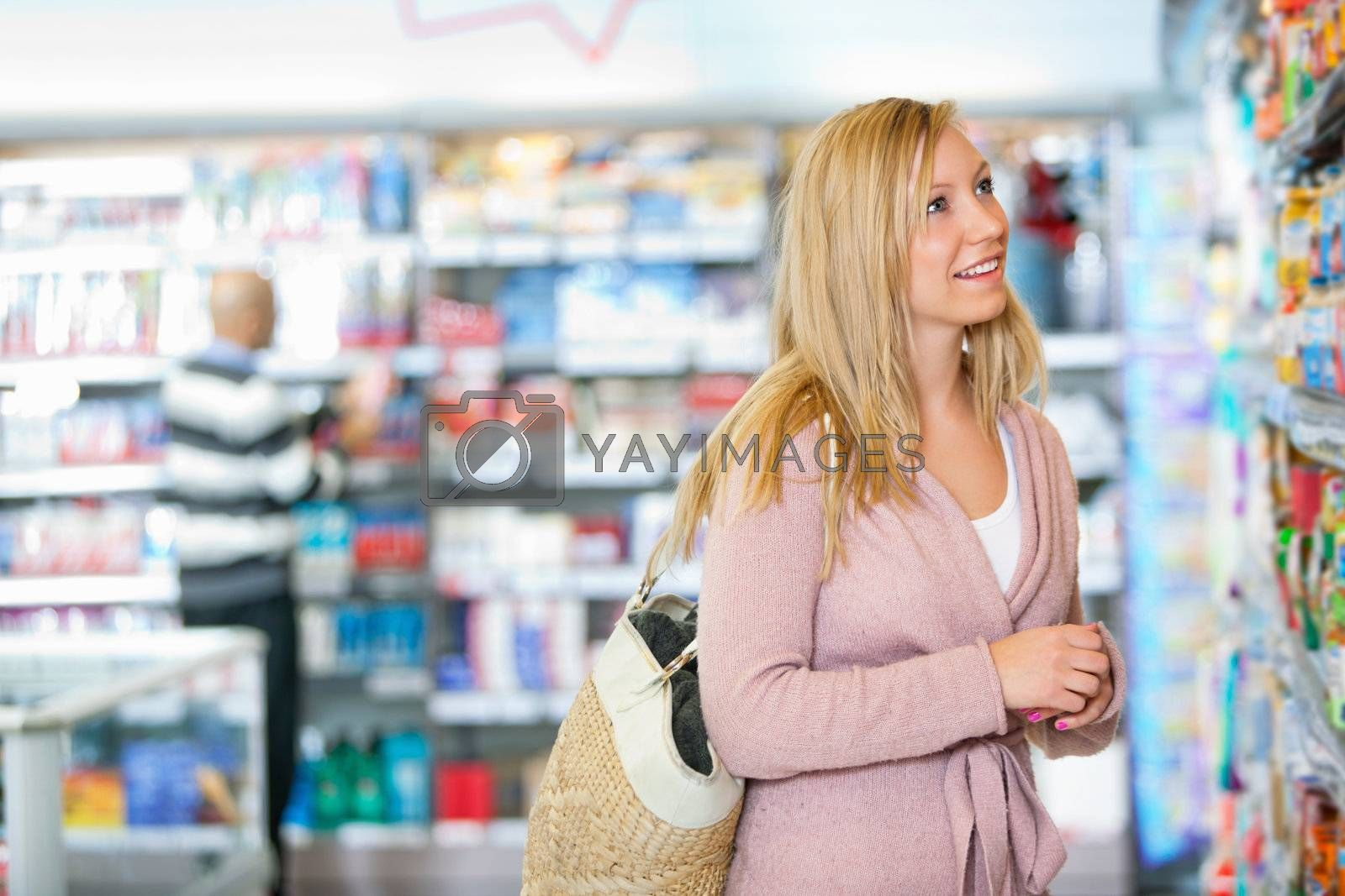 Young woman smiling while looking at goods in the supermarket with people in the background