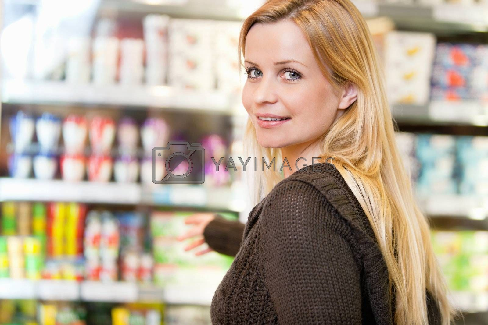 Close-up of smiling woman reaching for products arranged in refrigerator and looking at camera