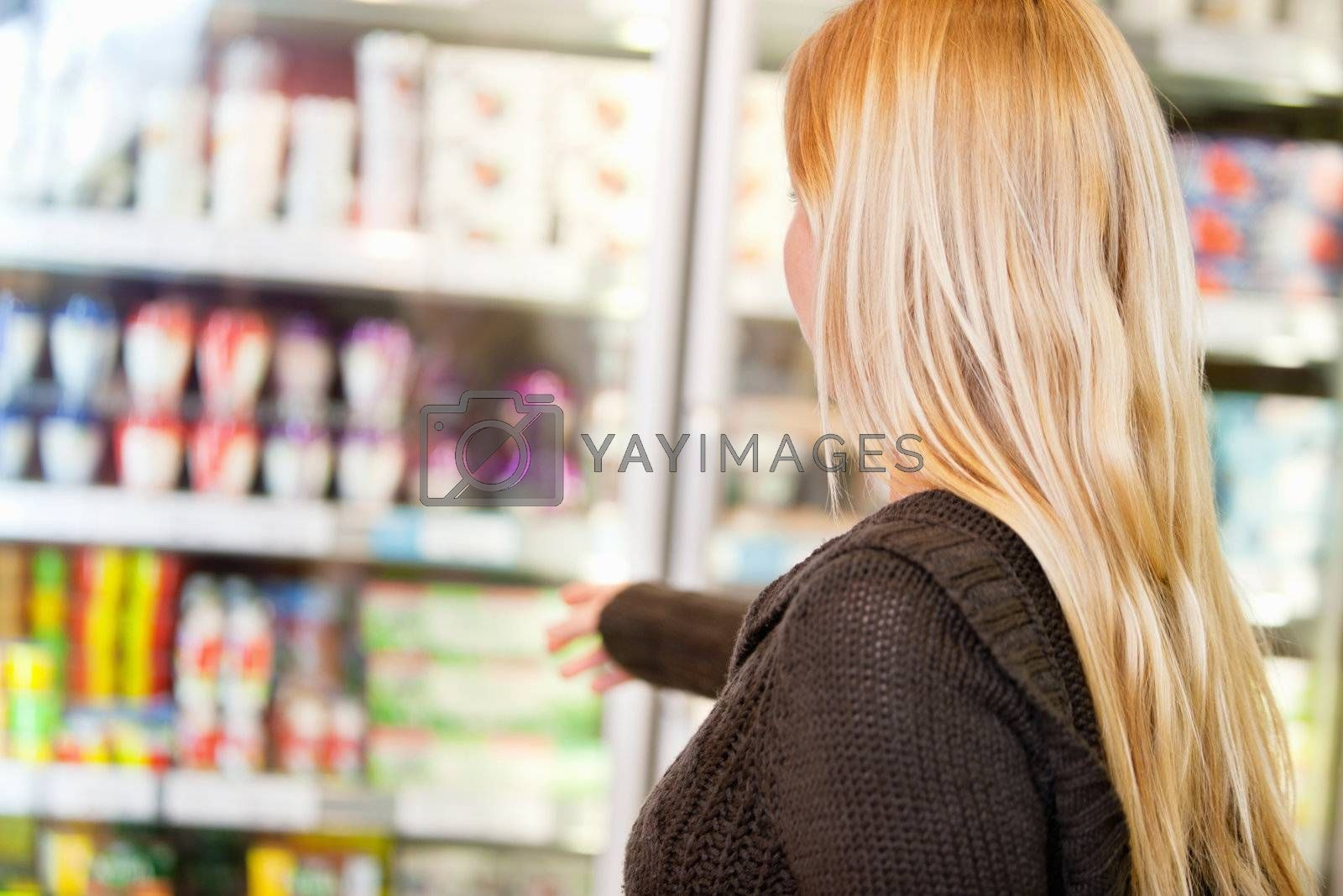 Close-up of woman reaching for products arranged in refrigerator