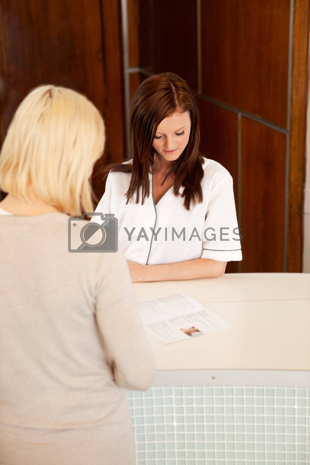 A woman in a spa reception looking at a brochure