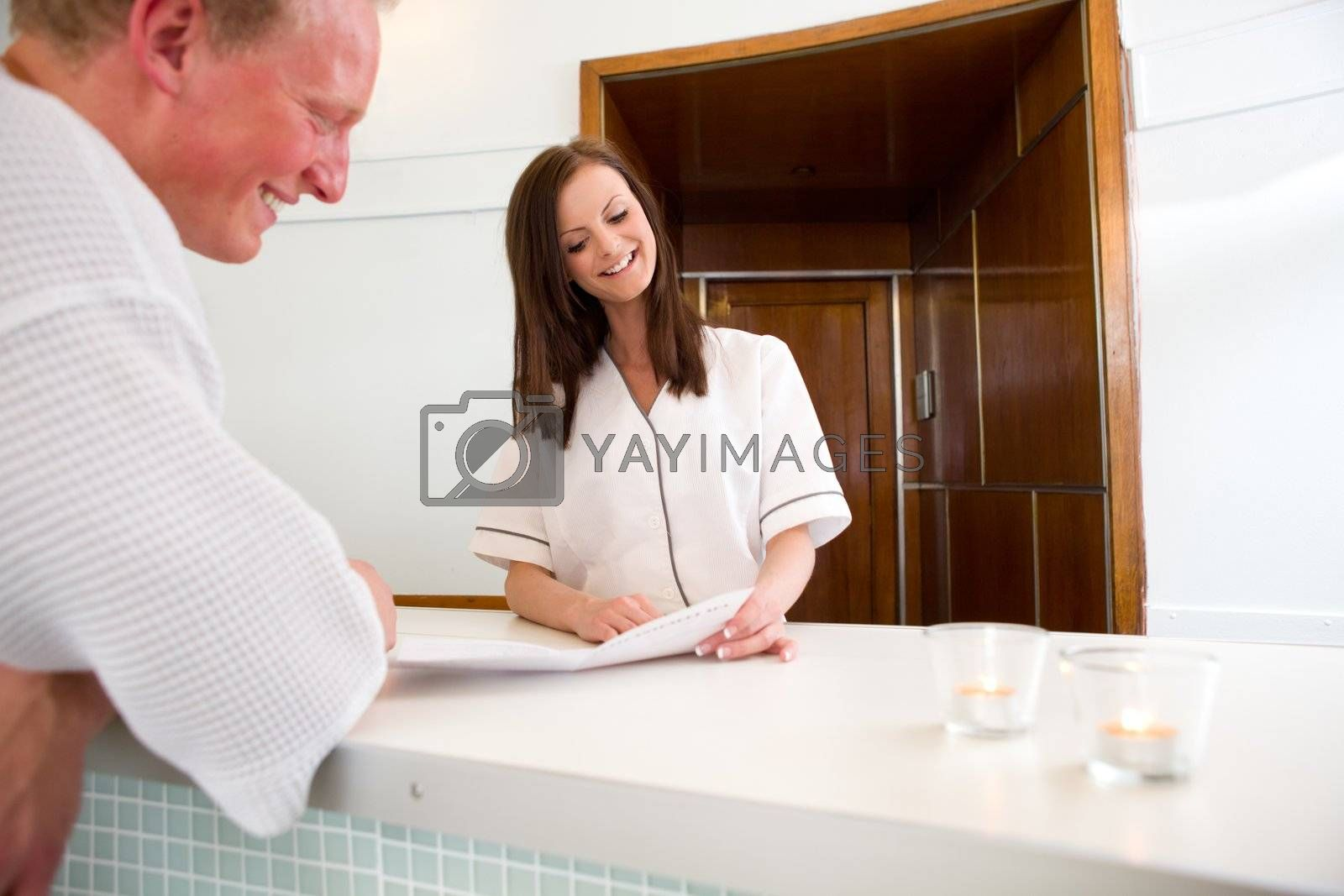 A man deciding on a package in a spa reception