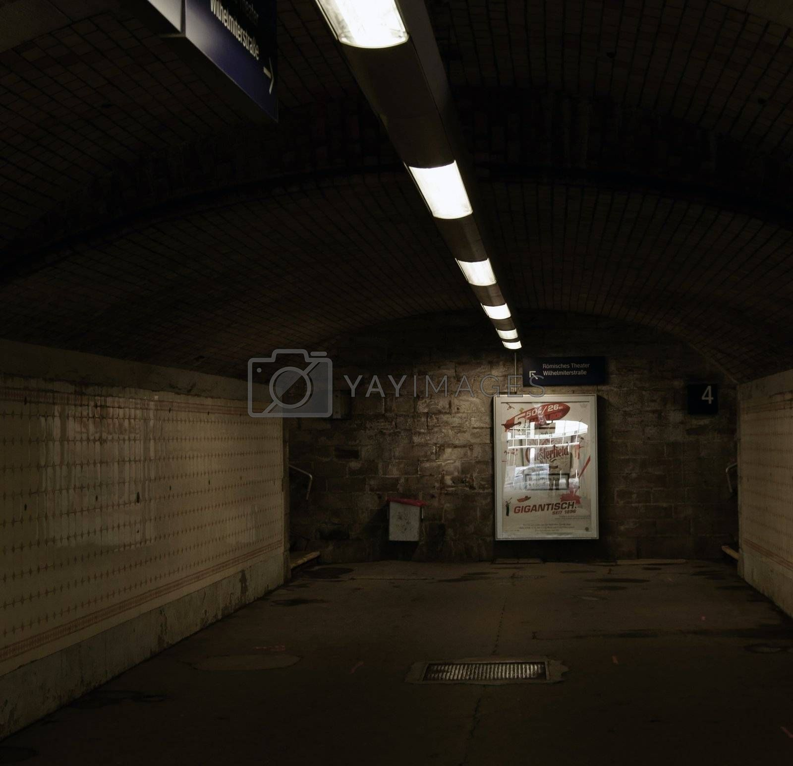 Dark tunnel from a station with artificial lighting and advertising.