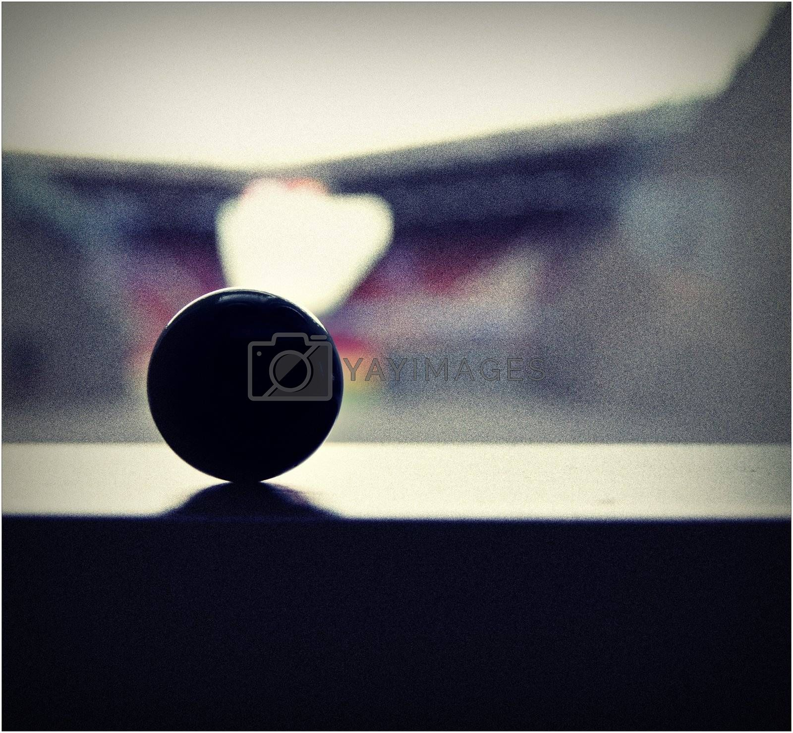The photograph of a small marble (ball) in front of a window overlooking a soccer stadium.