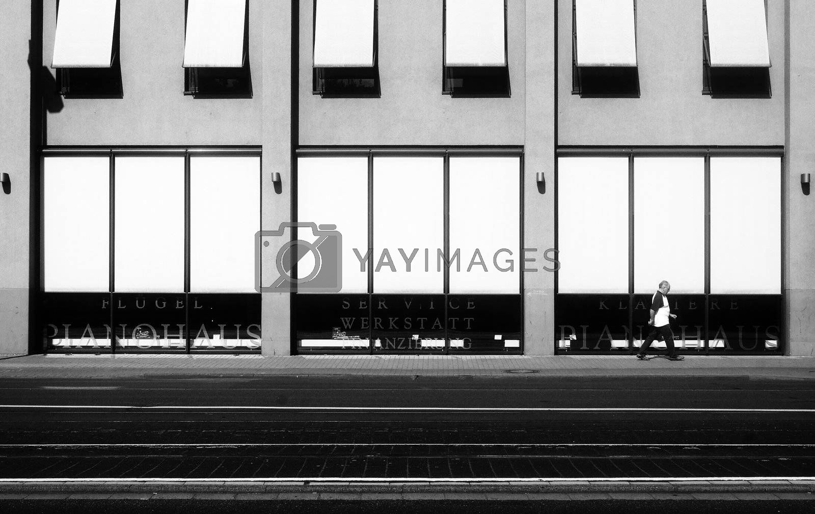 Pedestrian passes a piano store in the center of Mainz. Modern architecture