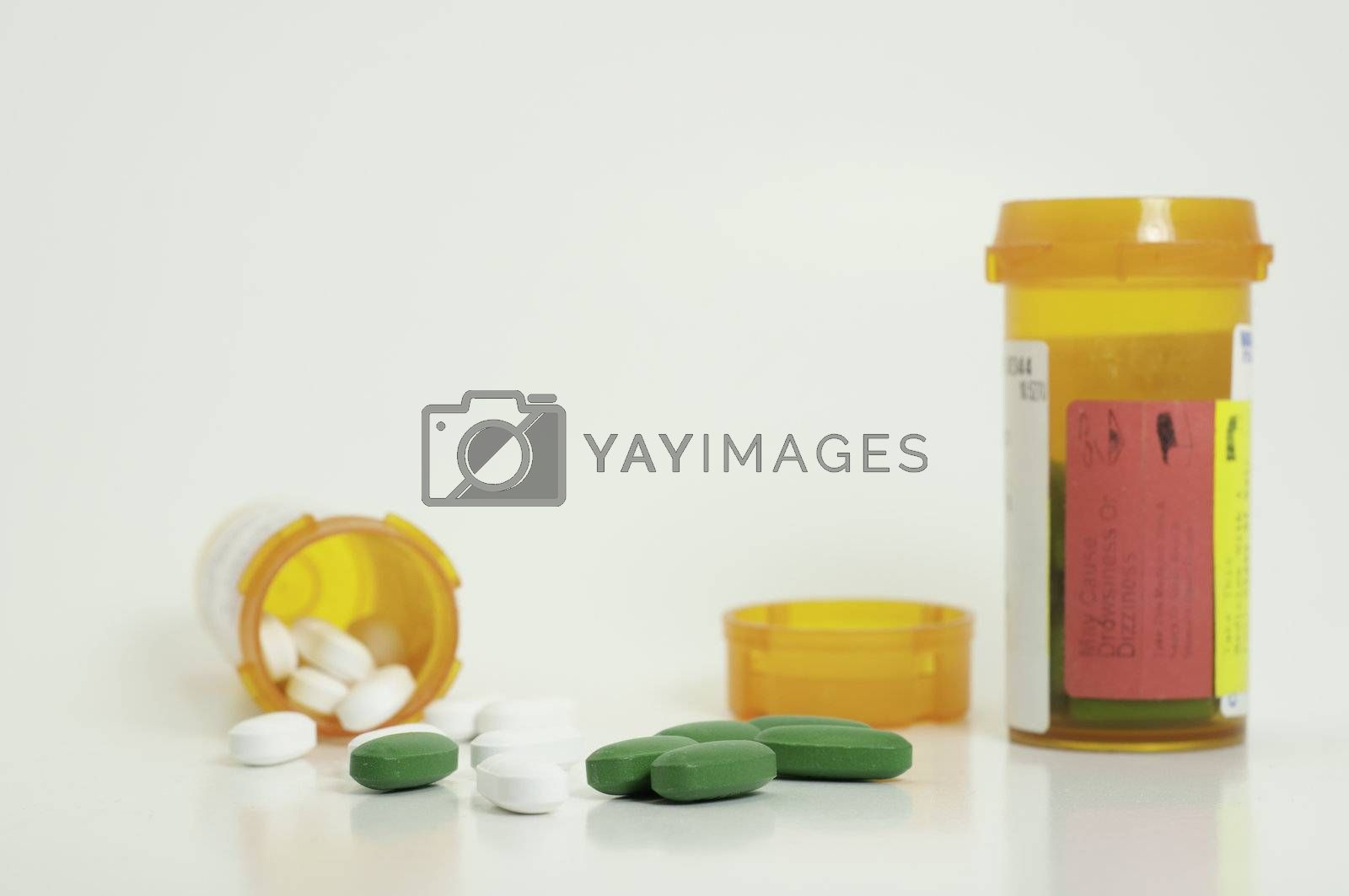 spilled white and green prescription pills with two bottles and a lid in background