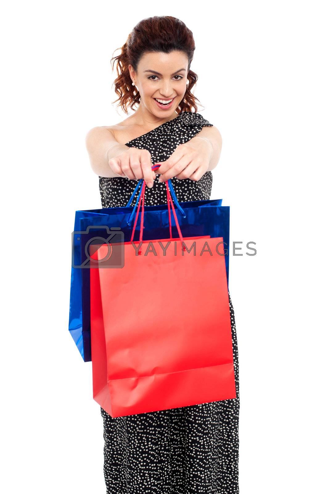 Cheerful young beautiful woman wearing a long black holding shopping bags