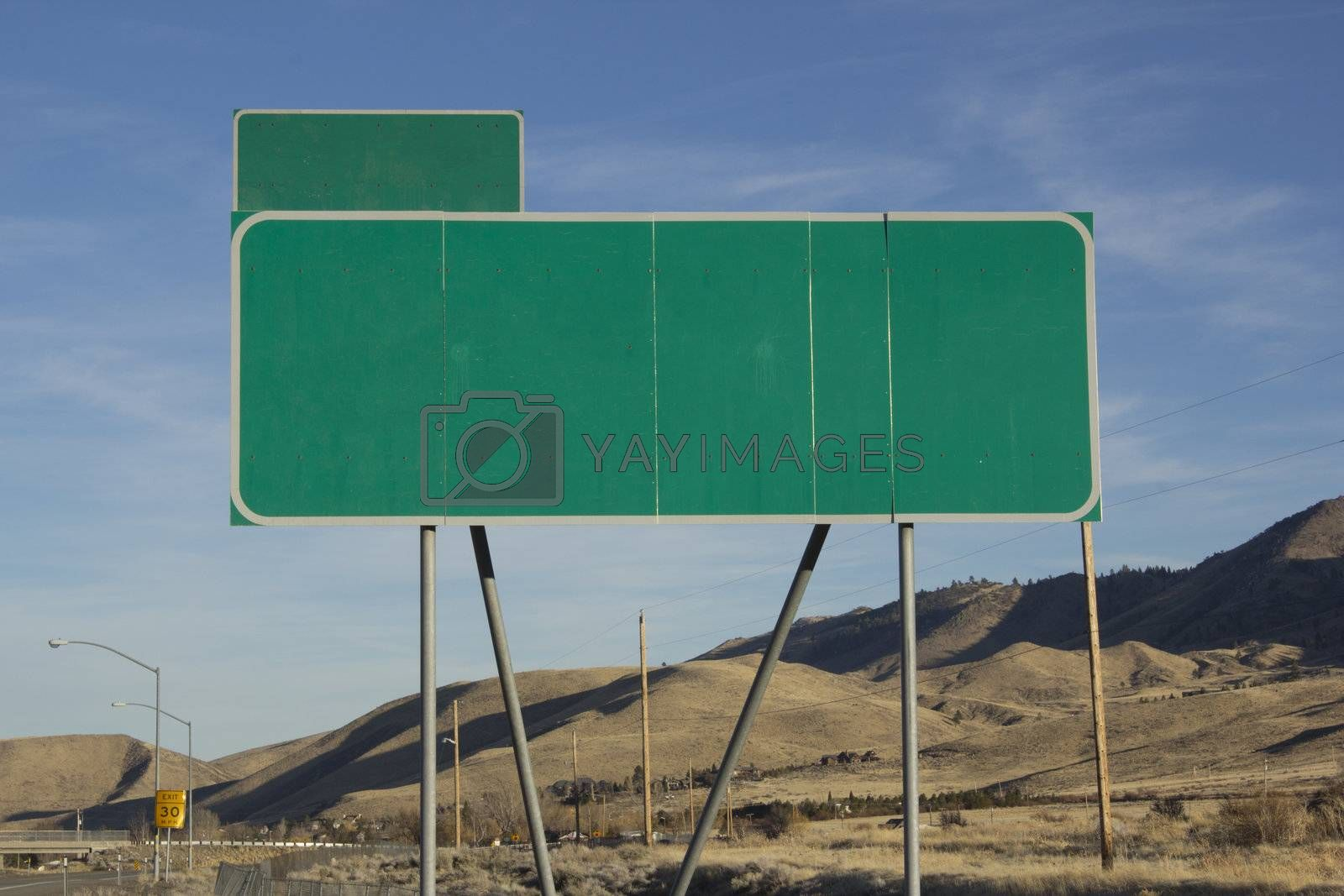 Green road sign with a blue sky and mountain background.