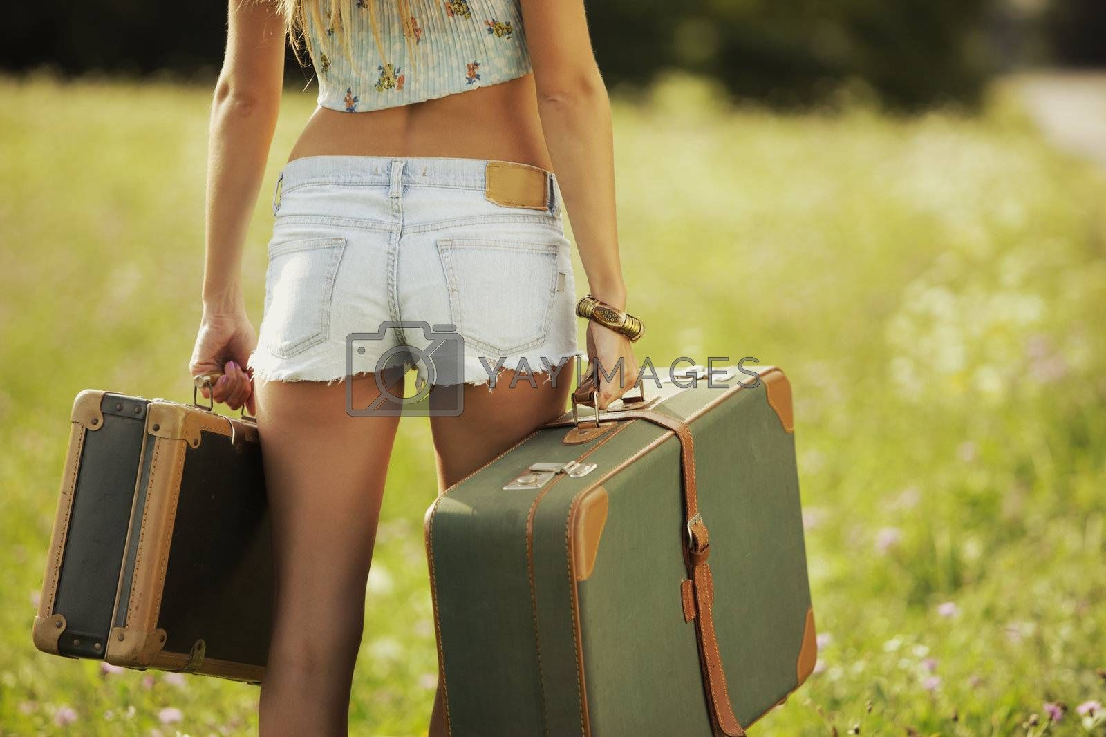 Sexy girl with suitcases, walking on a lawn