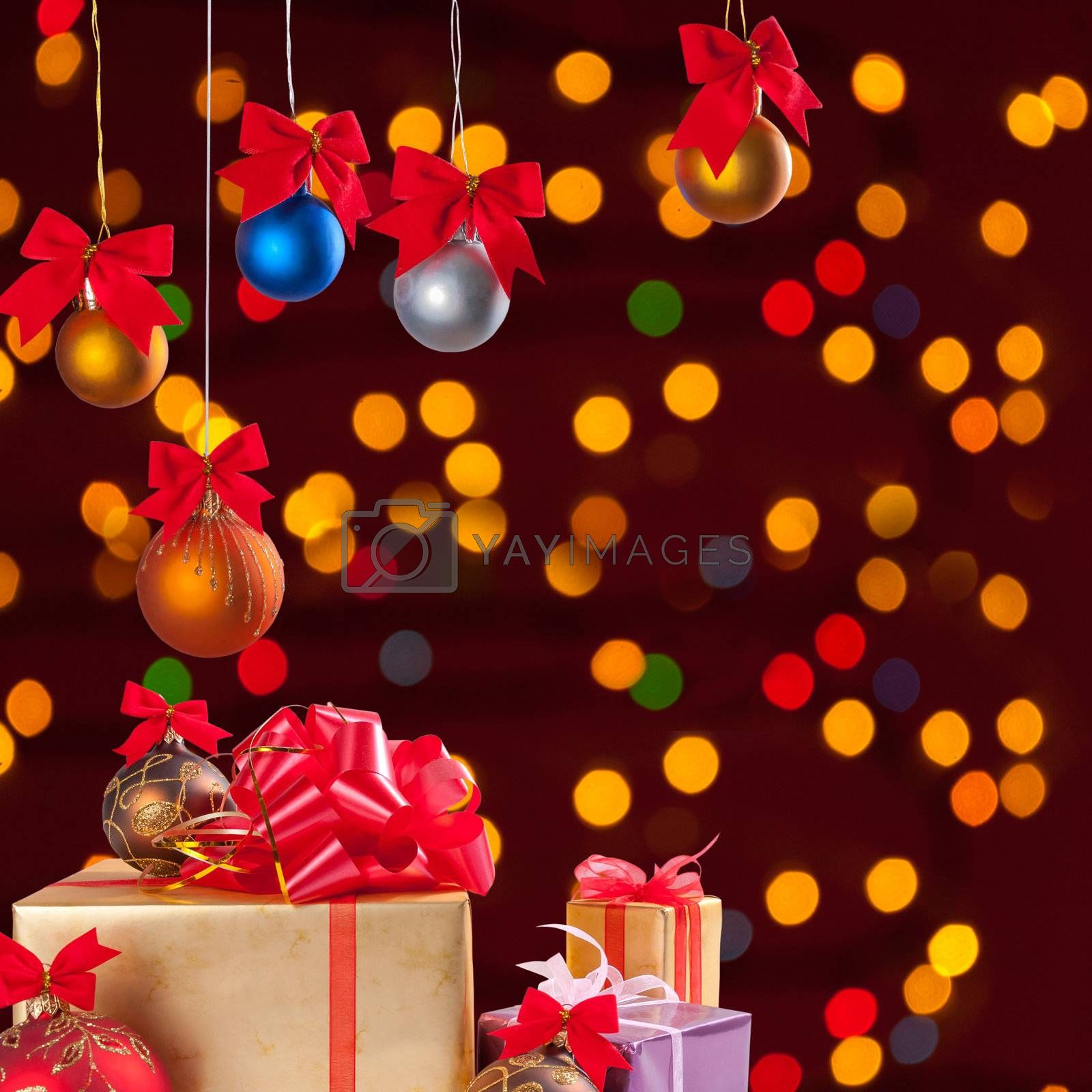 Christmas balls on ribbon and gifts on festive background